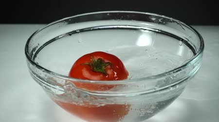 tomate cereja : Splashes of clean water from a falling ripe tomato at white background, Slow motion. One red tomato in a glass bowl on the table