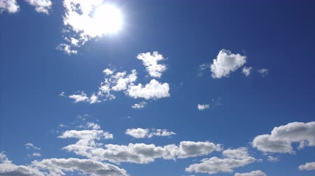 анатомический : Timelapse 4K, the Sun high above the white clouds in the blue sky. Beautiful cloudscape. Sunshine through the cloud