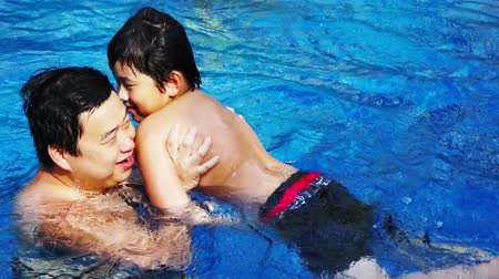 tombul : Asian Father and Son fooling around happily in the pool. Stok Video