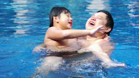 uszoda : Asian Father and Son chatting happily in the pool.