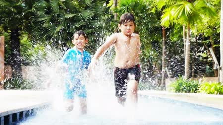 детеныш : Two asian boys playing and racing in the pool. Стоковые видеозаписи