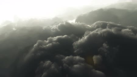 alkotás : Aerial flying above dark grey cloudy sky towards the sun