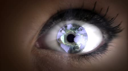jasno : Looping video direct close up shot of a woman with graphical earth rotating in her eyes. Dostupné videozáznamy