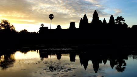 Time lapse sunrise silhouette shot of Angkor Wat with water reflection.