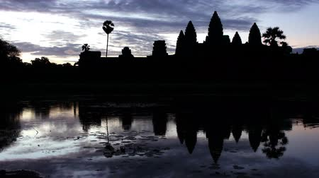 Time lapse evening silhouette shot of Angkor Wat with water reflection. Stok Video