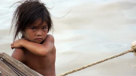 CAMBODIA ??�?���� May 2012: Young girl on a rough wooden boat sailing in Tonle Sap Lake in Cambodia in May 2012.  Living conditions in the area are difficult - Cambodia