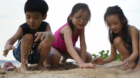 Siblings on the beach playing with Sand. Stok Video