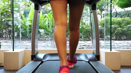 Back view of a lady running on treadmill.