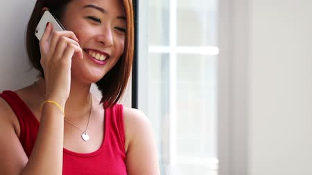 An Asian young lady making a phone call.