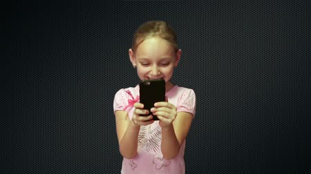 żart : A young girl read the phone and laughs. Wideo