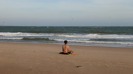 pozisyon : Young man sitting lotus position on beach. Stok Video