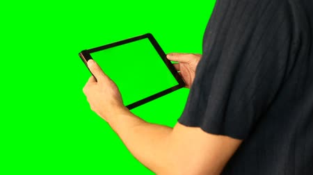 touchpad : Man using tablet with green screen doubled on big screen 3 from 5. Real shadow on screen.