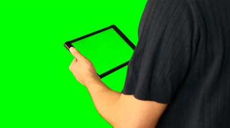 esquerda : Man using tablet with green screen doubled on big screen 4 from 5. Chroma key green screen. HD.