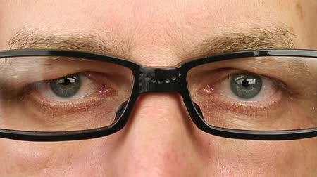 rectus : Adult man in eyeglasses extremely close-up view. Thinking looking around. Eye movement side to side. Corner of eyes. Smiling laughing man face w glasses. Think read see down up and side eyes motion Stock Footage
