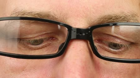 watching : Caucasian man in eyeglasses extremely close-up view. Thinking looking around. Eye movement side to side. Corner of eyes. Smiling laughing man face glasses. Think read see down up and side eyes motion Stock Footage