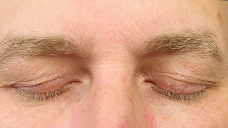 lidércnyomás : Sleeping adult man open his eyes. Extreme close-up view. Human eyes fast open up. REM rapid eye movement. See dreams sleep and wake up rapidly. Caucasian male face close open eyes. Ophthalmology. Stock mozgókép