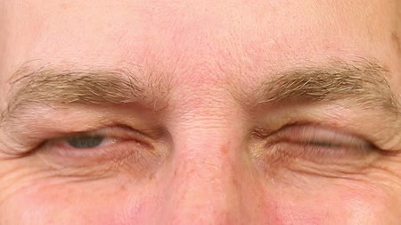 calçadão : Adult man laughing with eyes. Extreme close-up view. Wrinkles around the eyes from laughing. The mans eyes narrowed. Human eyes fast open up and shut down. Caucasian male face close open eyes.