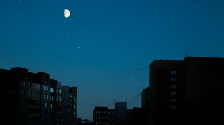 световой люк : Moon swim at dark blue sky above night city. Appartment block sweet dream looking. Sweet sleep dream time. Night time flickering stars sky. Rising moon summer night over city skyline stars sparkling