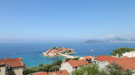 st stephen : Sveti Stefan island panning by horizon. Seacoast with old stone buildings. Sunny day blue sky clouds. Top view resort seashore. Sea coast line horizon.
