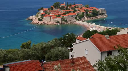 st stephen : Sveti Stefan island tilting up. View blue sea water to horizon. Seacoast with old stone buildings. Sunny day blue sky clouds. Top view resort seashore. Sea coast line horizon.