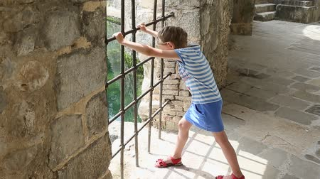 jailed : Young girl shake grill. She want go out. Need freedom. Young girl - prisoner in chateau. Stock Footage