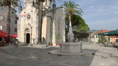 st michael the archangel : Herceg Novi, Montenegro - 31 June, 2017. Church St. Michael Archangel Herceg Novi with fountain nearby. High palm trees. Old city fortress church Topla sunny summer day. Stock Footage