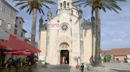 st michael the archangel : Herceg Novi, Montenegro - 31 June, 2017. Church St. Michael Archangel Herceg Novi. High palm trees. Old city fortress church Topla sunny summer day. Tilting shot up to blue sky.