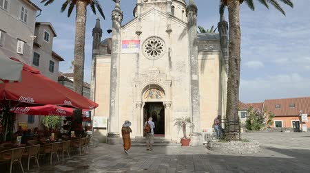 st michael the archangel : Herceg Novi, Montenegro - 31 June, 2017. Church St. Michael Archangel Herceg Novi. Man and woman tourists are baptized before entering temple. Orthodox Christianity in Montenegro.