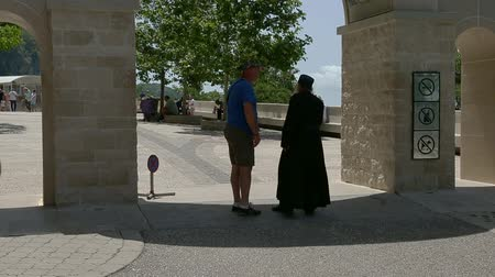 clergyman : Ostrog, Montenegro - 30 June, 2017. Priest speaking with parishioner at entrance arch near Ostrog monastery. Arch entrance to Ostrog monastery in mountains Montenegro. Christian monastery and church.