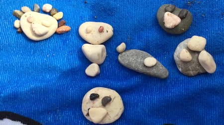 toalha : Small child laying out shingle pebbles on beach. Funny mugs are obtained from stones on beach. Smile symbol is background for vacation relax and calm.