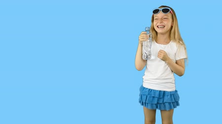 řev : Little girl falls from laughing. Girl laughs and holds a bottle of water in her hands. Girl in sunglasses and a T-shirt. Clip with Premultiplied matted Alpha Channel. Transparent background PNG format