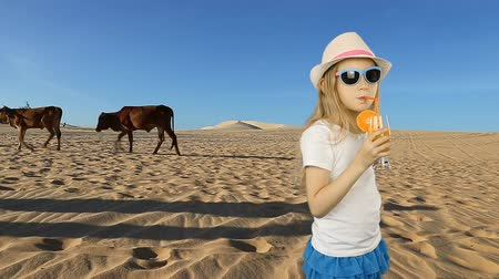 szomjúság : Young caucasian girl drink orange juice. Young girl in sahara desert feeling thirst. Very hot warm climat in desert. Fresh juice of orange fruit drinking walking in hat summer day.