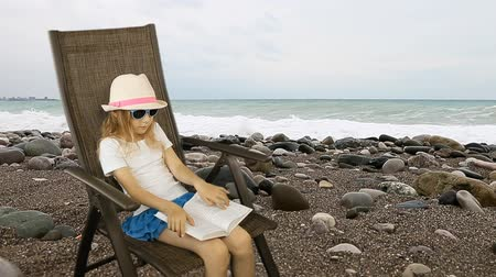 pedregulho : Young caucasian girl sitting on armchair and reading book. Sea horizon on background and pebble stones foreground. Have same clip with transparent background Alpha Channel. Stock Footage