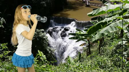 aventura : A young girl stands near a waterfall in the jungle and drinks crystal clear water from a bottle. A tropical forest and a huge waterfall. Have same clip with transparent background Alpha Channel.