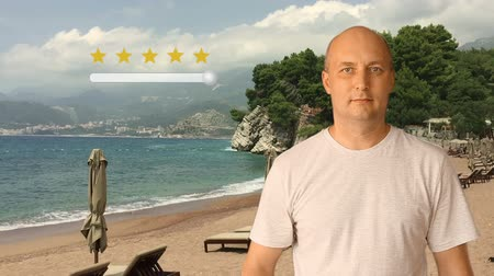 ocena : Feedback five stars from man on virtual screen. Man standing on sunny beach. Man move slider to set rating of services from one to five star. Caucasian man smiling and show thumbs up.