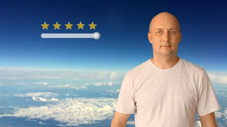 ocena : Score of 5 stars on a virtual screen. The man moves his finger on the virtual screen. Against a blue sky with clouds on a sunny day. The white man shows satisfaction. Wideo