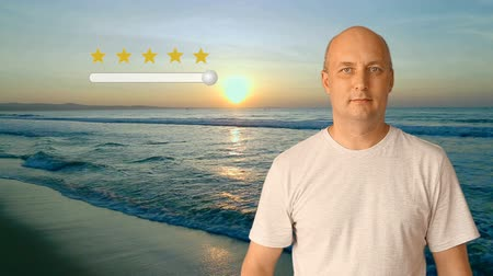 ocena : An adult man standing on the beach by the sea at sunset shows an excellent rating for the resort. A high score of 5 stars for the beach is long and beautiful.
