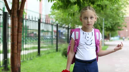 żart : Young pretty girl standing near school with backpack and flowers sunny day. Back to school. Schoolgirl go to study. Primary school outdoors green trees. Wind Girl with flowers standing school.