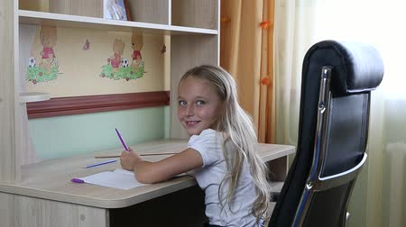 küçük kız : Left-handed girl sitting on chair by desk table and writing by pen in paper notebook. Back to school. Young caucasian girl smiling. Sit by table. Write by pen. White girl schoolgirl make home work.