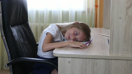 żart : Girl lying on table. Young girl tired study. Caucasian girl lying down. Sad face closeup shot. Back to school concept. Sitting on black chair by wooden table. Tap ones fingers by table. Wideo
