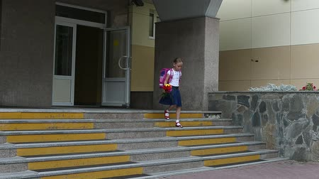 buket : Girl walking down stairs with backpack and flowers bouquet from school door. Back to school concept. summer day hanheld shot. Girl with a bouquet of flowers walking on the background of the school.