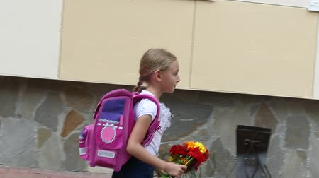 buket : Sorrowful girl go back to school with backpack and bouquet flowers. Young white caucasian girl with pink baclpack walking along stone wall of school. Handheld shot walking serious elementary girl.