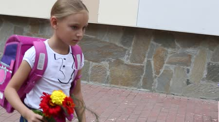 dismay : Sorrowful girl go back to school with backpack and bouquet flowers. Girl fright some thing at flowerbed. Young white caucasian girl with pink baclpack walking along stone wall of school. Handheld shot Stock Footage