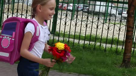 vigyorgó : Happy young girl go back to school with pink backpack and bouquet of flowers. Sunny day outdoors handheld shot. Girl walking along iron fence and green grass. Back to school concept.