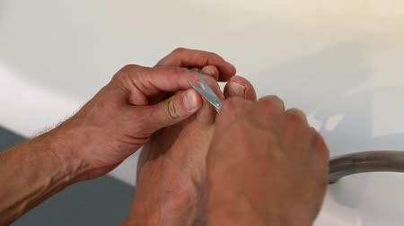 pinky : Man cutting toenails with scissors on bathtub. Male cut toenails on foot. Clip toenails close up. Stock Footage