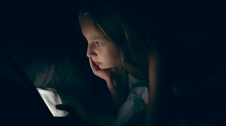 watching : Young caucasian white girl watching video lying in bed at night. Elementary girl looking movie by mobile tablet.