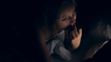 gadżety : Pensive young girl thinking and touch lips and mouth with hand. Caucasian girl with tablet in bed night. Wideo