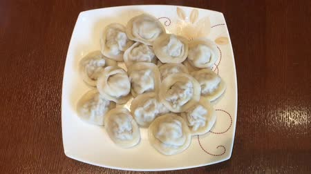 пельмени : Beige plate of hot homemade meat dumplings on the table. Jet of steam. Top view handheld shot