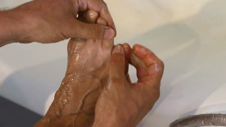índice : Man wash his feet with soap by hand in bathroom. Closeup locked shot of male washing foot.