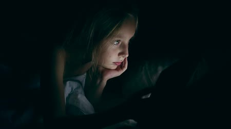 кровать : Sad young school girl using tablet pc in the night in her bed and looking at tablet screen tired and serious.